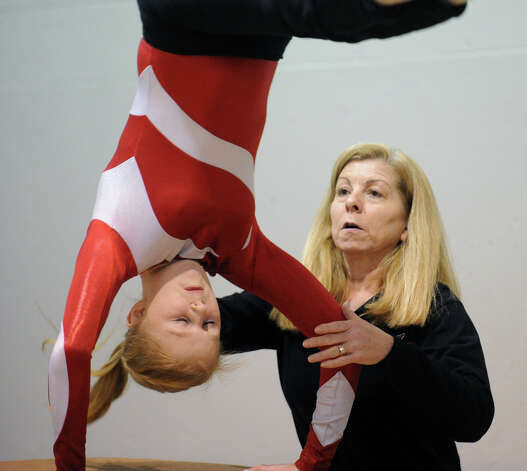 Greenwich gymnastics coach Sue Knight, right, spots her gymnast Hannah Klein in a vaulting warm-up prior to the start of the girls gymnastics meet between Staples High School and Greenwich High School at the YWCA in Greenwich, Thursday afternoon, Jan. 17, 2013. Photo: Bob Luckey / Greenwich Time