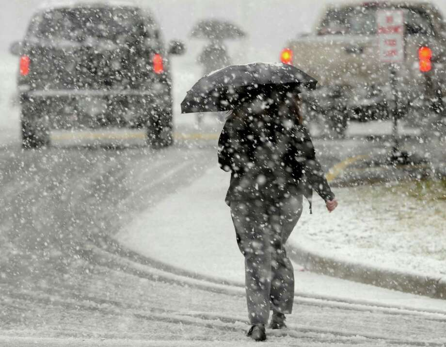 A Food City employee uses an umbrella to stay dry as she goes to work during a heavy snowfall Thursday afternoon in Bristol, Va. as shoppers make a last-minute trip to the grocery store.  (AP Photo/The Bristol Herald-Courier,Andre Teague ) Photo: ANDRE TEAGUE