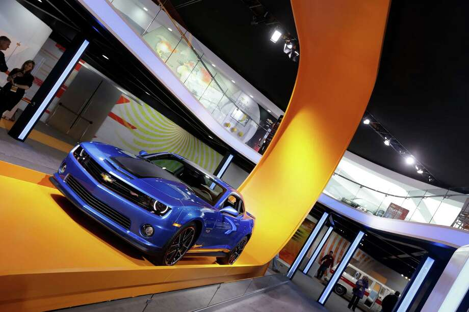 The Hot Wheels edition of the Chevrolet Camaro sits on an oversized track that appears to swoop down from the ceiling at the North American International Auto Show in Detroit, Tuesday, Jan. 15, 2013. General Motors Co. last year announced it would sell the vehicle with Hot Wheels logos and other toy-inspired touches such as red-lined wheels. (AP Photo/Carlos Osorio) Photo: Carlos Osorio, Associated Press / AP