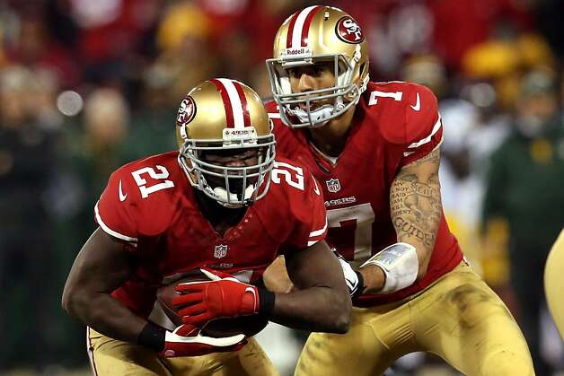 Colin Kaepernick hands the ball off to Frank Gore on Saturday against Green Bay. The two ran the read-option brilliantly, with the quarterback gaining 181 yards rushing and Gore 119. Photo: Stephen Dunn, Getty Images