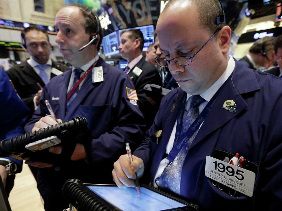FILE - In this Thursday, Jan. 10, 2013, file photo, Jeffrey Vazquez, right, works with fellow traders on the floor of the New York Stock Exchange. Stock futures jumped Thursday, Jan. 17, 2013,  as the government reported that weekly applications for unemployment benefits hit a five-year low and the construction of new homes surged. (AP Photo/Richard Drew) Photo: Richard Drew