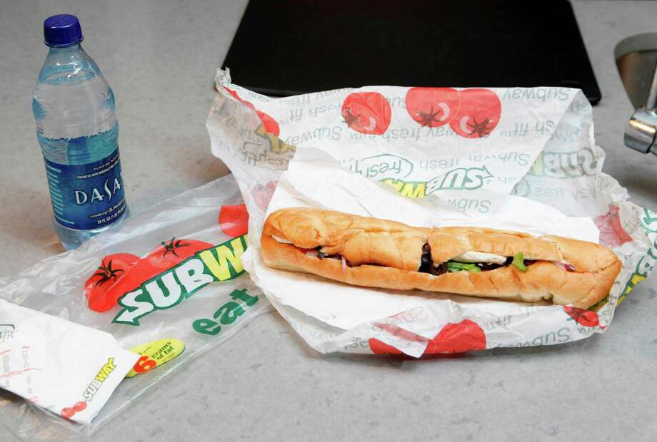 FILE - This Aug. 11, 2009, file photo, shows a chicken breast sandwich and water from subway on a kitchen counter in New York. Subway, the world's largest fast food chain, is facing criticism after an Australian man posted a picture on the company's Facebook page on Jan. 16, 2013, of one of its famous sandwiches next to a tape measure that seems to shows it's not as long as promised.  (AP Photo/Seth Wenig, File) Photo: Seth Wenig