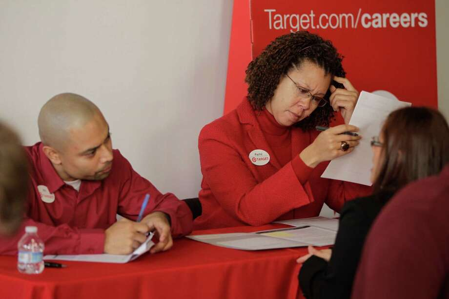In this Thursday, Jan. 10, 2013, photo, Target human resources executives Will Castro, left, and Rachel Ferguson, middle, screen hundreds of prospective candidates awaiting their turn to apply for job openings at a Target job fair in Los Angeles. The number of Americans seeking unemployment aid fell to a five-year low last week, a hopeful sign the job market is healing. But much of the decline reflects seasonal volatility in the data. (AP Photo/Damian Dovarganes) Photo: Damian Dovarganes