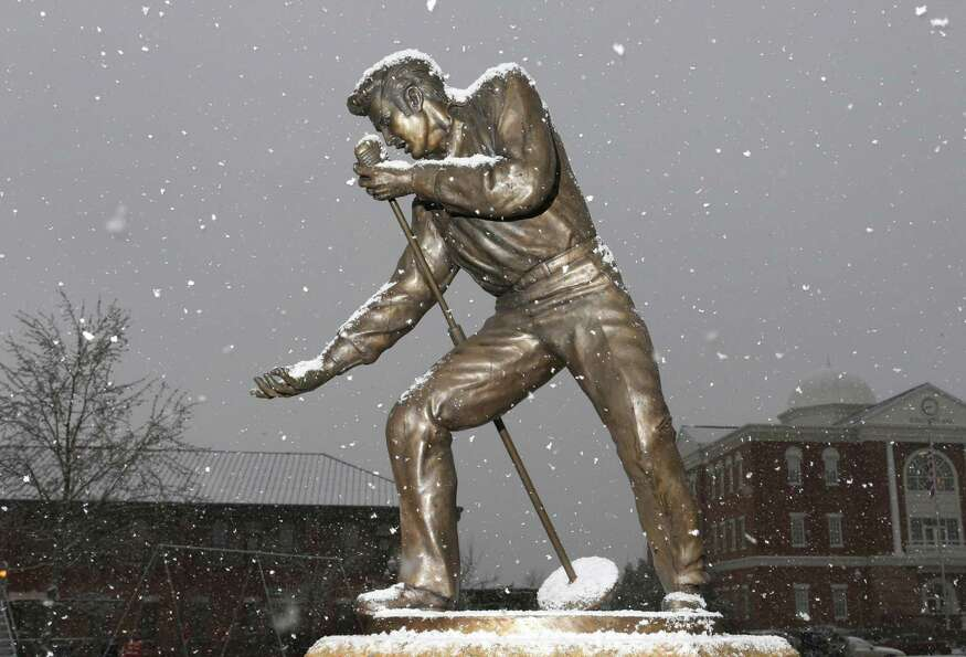 Snow falls on an Elvis Presley statue in downtown Tupelo, Mississippi on Thursday, Jan. 17, 2013.  A
