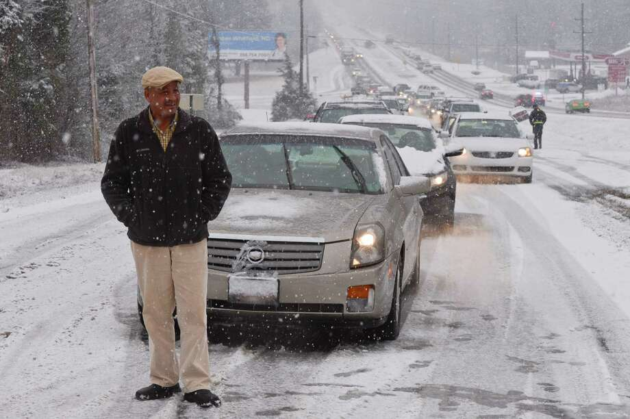 Heavy snow falls in Hartselle, Ala., causing many traffic problems and some fun for children Thursday, Jan. 17, 2013.  Motorist James Burton stands in front of his car stranded on US Highway 31 on Hartselle Mountain after the stretch of highway became to slick for many motorists to get up the hill. Photo: Gary Cosby Jr., Associated Press / The Decatur Daily