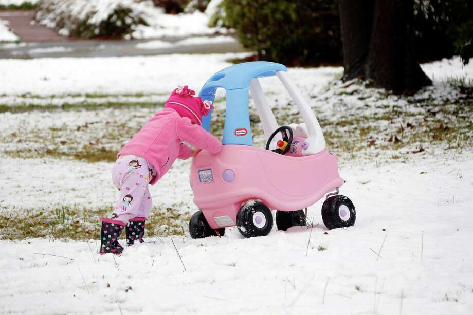 Molly Cleland, two and a half,  pushes her car through the snow in Jackson, Miss., Thursday,  Jan. 17, 2013.  A winter storm system left 2 to 4 inches of snow in parts of central Mississippi before heading east toward Alabama, the National Weather Service said. Photo: Rogelio V. Solis, Associated Press / AP