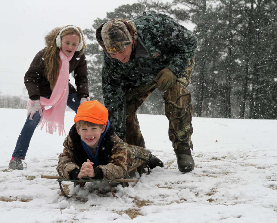 Sarah Paige Shirley, left, watches as L. J. Fruge pushes his son, Jay, down a hill in the snow Thursday, Jan. 17, 2013, at Northwood Country Club in Meridian, Miss. The snow that lightly covered the area was all melted by late morning. Photo: Paula Merritt, Associated Press / The Meridian Star
