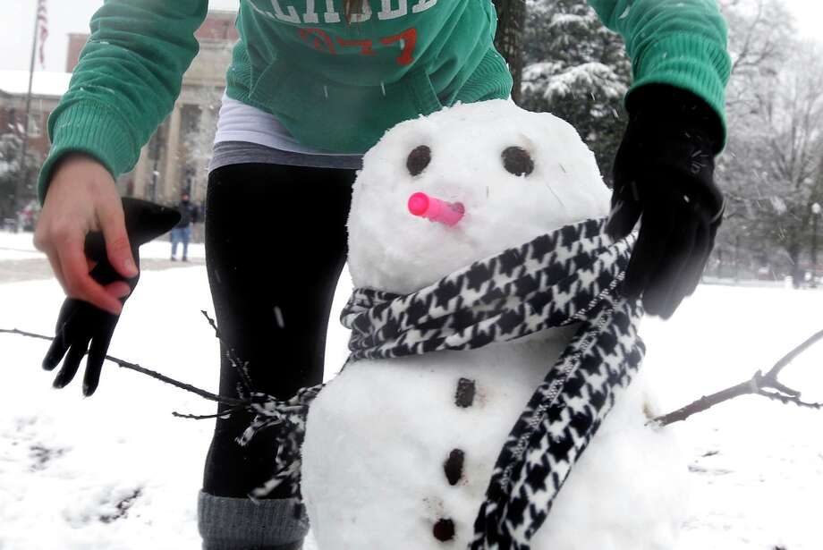 A University of Alabama student ties a houndstooth scarf around a snowman on the quad on Thursday afternoon Jan. 17, 2013 in Tuscaloosa, Ala. Hundreds of students gathered at the quad as the heavy snow fall coated Tuscaloosa. Photo: Robert Sutton, Associated Press / The Tuscaloosa News