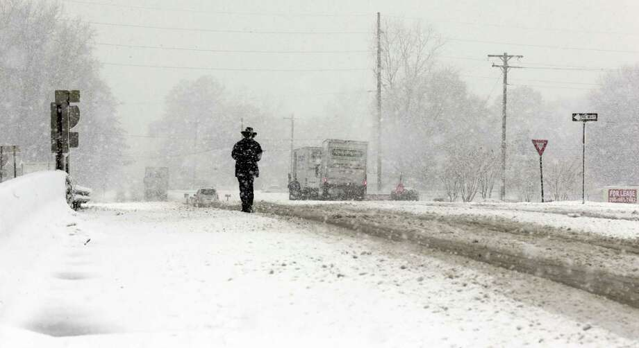 A pedestrian walks along snow covered roads in Hartselle, Ala., Thursday, Jan. 17, 2013. Snow fell in Central and North Alabama, sending kids home from schools early along with other closures. Photo: Dave Martin, Associated Press / AP