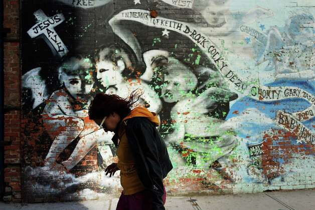 NEW YORK, NY - JANUARY 17:  A woman walks by a graffiti memorial on a wall in memory of individuals killed in the Bedford-Stuyvesant neighborhood on January 17, 2013 in the Brooklyn borough of New York City. Visual memorials honoring residents who in many cases met violent ends decorate many Brooklyn neighborhoods. New York Governor Andrew Cuomo recently signed into law the New York Secure Ammunition and Firearms Enforcement Act, one of the toughest gun laws in the country. (Photo by Spencer Platt/Getty Images) Photo: Spencer Platt