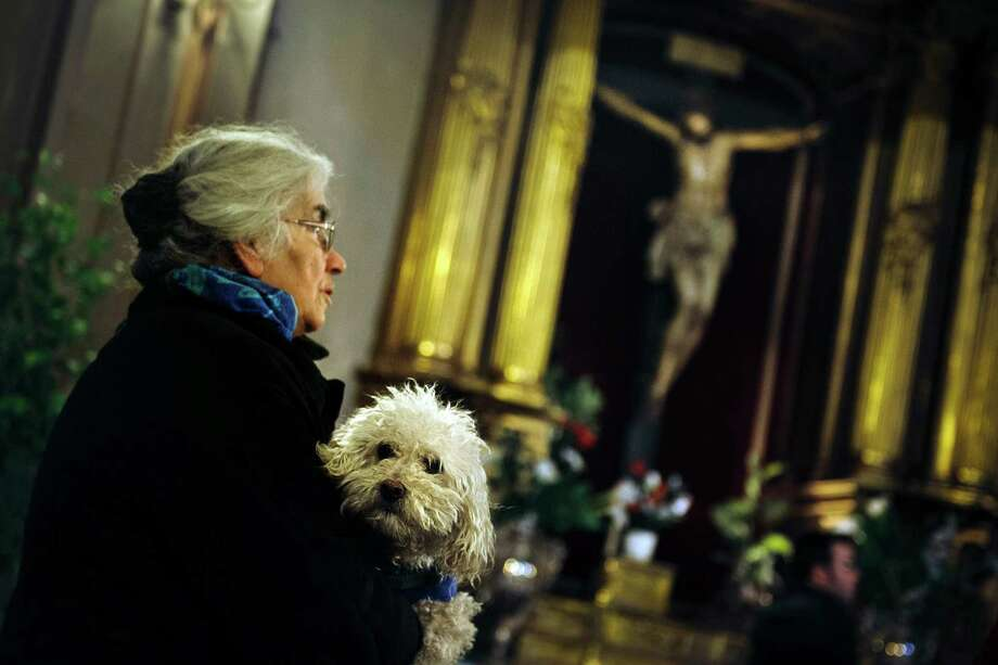 A woman holding her dog takes part in a mass at San Anton Church in Madrid, Thursday, Jan. 17, 2013, in honor of Saint Anthony, the patron saint of animals. The feast is celebrated each year in many parts of Spain and people bring their pets to churches to be blessed. Photo: Daniel Ochoa De Olza, Associated Press / AP