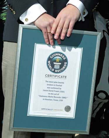 "Guinness World Records, Head of US Records Management Mike Janela holds the world record certificate after Jason David Frank  broke the ""Most pine boards broken in freefall""  Guinness World Record. Photo: James Nielsen, Chronicle / © Houston Chronicle 2013"