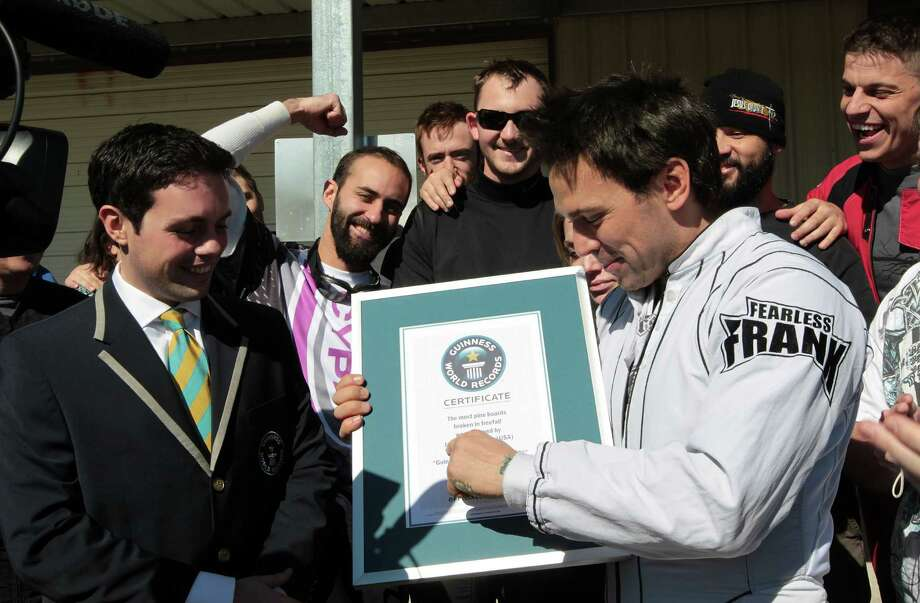 "Guinness World Records, Head of US Records Management Mike Janela, left, presents the world record certificate to Jason David Frank right, after Frank broke the ""Most pine boards broken in freefall""  Guinness World Record while skydiving at Skydive Spaceland Thursday, Jan. 17, 2013, in Rosharon. Photo: James Nielsen, Chronicle / © Houston Chronicle 2013"