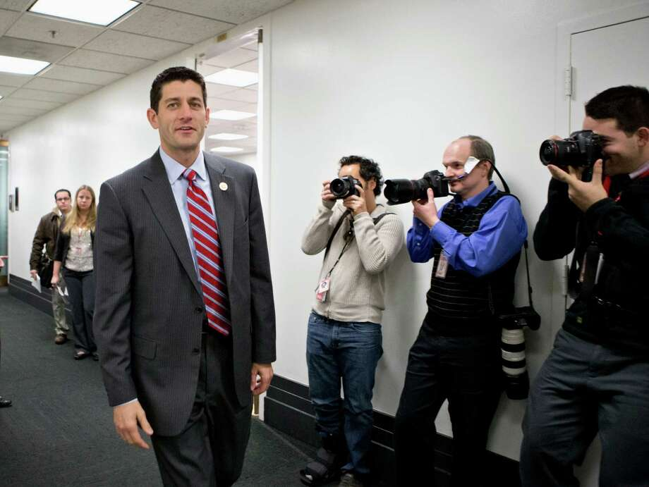 FILE - This Nov. 28, 2012 file photo shows House Budget Committee Chairman Rep. Paul Ryan, R-Wis. walking on Capitol Hill in Washington.  House Republicans say they may seek a short-term extension of the government's debt limit in the next few weeks, a move that would avoid an immediate default by the Treasury. Ryan provided no details on the duration of any extension or conditions that might be attached as he appeared at a news conference during a break at a three-day retreat of the rank and file in historic Williamsburg, Va.  (AP Photo/J. Scott Applewhite, File) Photo: J. Scott Applewhite