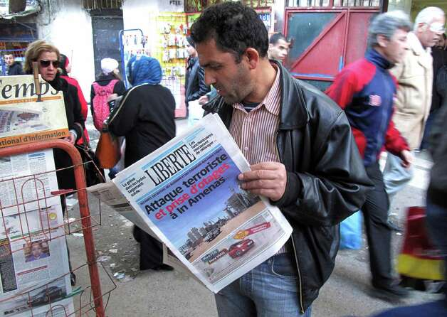 "A man reads a newspaper headlining ""Terrorist attack and kidnapping in In Amenas"", at a news stand in Algiers, Thursday, Jan. 17, 2013. Algerian forces raided a remote Sahara gas plant on Thursday in an attempt to free dozens of foreign hostages held by militants with ties to Mali's rebel Islamists, diplomats and an Algerian security official said. Information on the Algerian assault in the remote area was wildly varying _ Islamic militants claimed that 35 hostages and 15 militants died in a strafing by Algerian helicopters, while Algeria's official news service claimed hundreds of local workers and half the foreigners were rescued. (AP Photo/Ouahab Hebbat) Photo: Ouahab Hebbat"