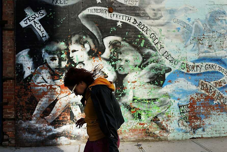 A woman walks by a graffiti memorial on a wall in memory of individuals killed in the Bedford-Stuyve