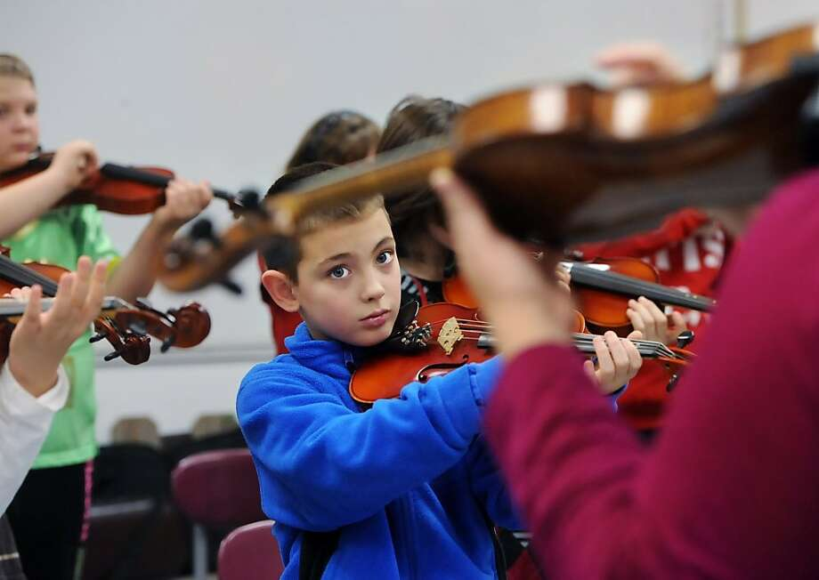 Fourth-grader Parker Freels, 9, watches Elizabeth Jones while learning the pizzicato technique on a violin Thursday morning, Jan. 17, 2013 at Newton Parrish Elementary School in Owensboro, Ky.. Jones, with the Owensboro Symphony Orchestra, taught the children the basics of playing the violin. The students participated in the symphony's Strings Attached program. Photo: John Dunham, Associated Press