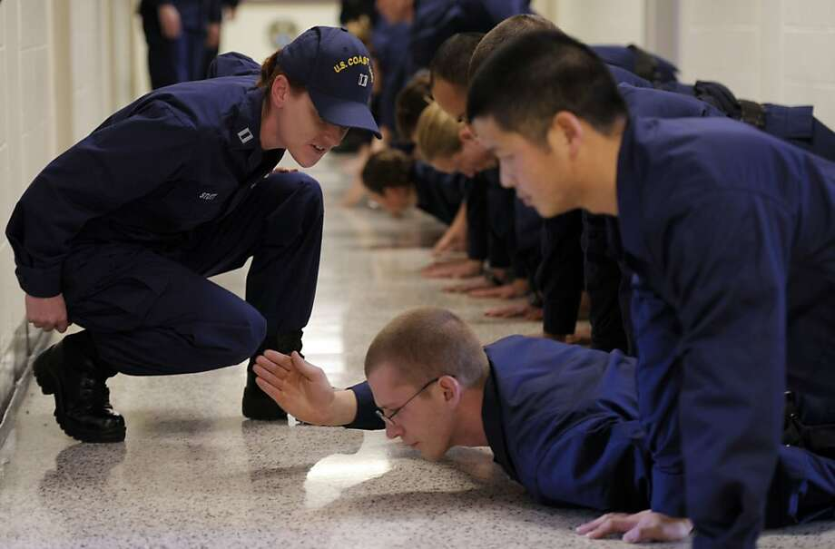 United States Coast Guard Lt. Rachel Stutt, left, asks an officer candidate why he is the only OC on the floor as Coast Guard and National Oceanographic and Atmospheric Administration (NOAA) officer candidates are drilled by their Coast Guard Officer Candidate School instructors Thursday, January 17, 2013 at the U.S. Coast Guard Academy in New London, Conn. This is the first time the Coast Guard and NOAA officer candidates have been trained together in a fully-integrated class. Photo: Sean D. Elliot, Associated Press