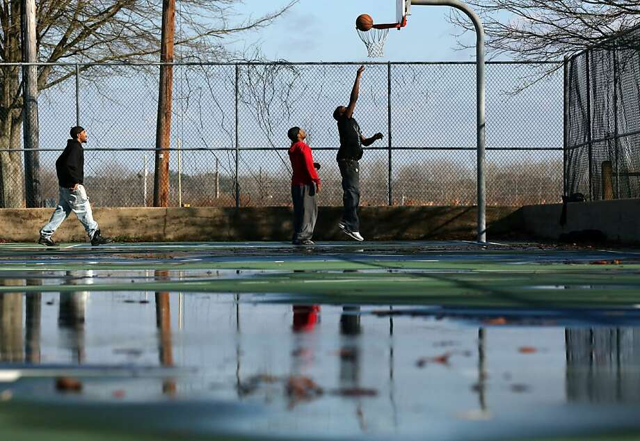 With rain and melted snow still on the court, from left, Davion High, Darion High and Marcus Collins shoot hoops at Old Mill Town Park in downtown Tupelo, Miss. on Thursday, Jan. 17, 2013. Due mostly to the recent inclement weather, the trio said that Thursday was the first time they have used the court this year. Photo: C. Todd Sherman, Associated Press