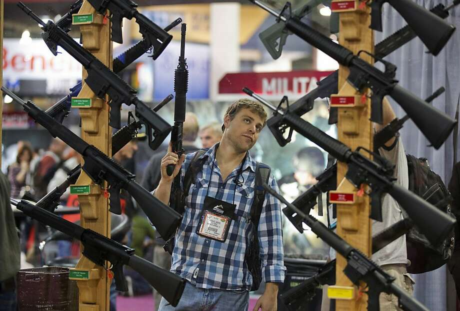 Michael Kiefer, of DeFuniak Springs, Fla., checks out a display of rifles at the Rock River Arms booth during the 35th annual SHOT Show, Thursday, Jan. 17, 2013, in Las Vegas. The world's largest gun and outdoor trade show runs through Friday. Photo: Julie Jacobson, Associated Press