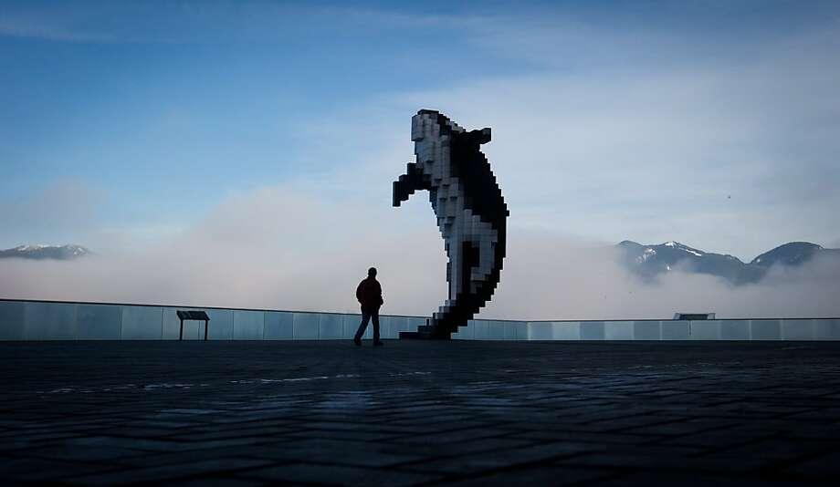 A man walks past Douglas Coupland's Digital Orca sculpture as marine fog hangs over the harbor in Vancouver, British Columbia, Canada, on Thursday, Jan. 17, 2013. Photo: Darryl Dyck, Associated Press
