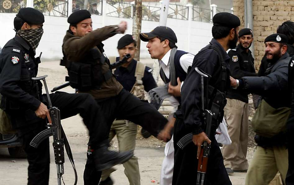 Pakistani police commandos kick a young adult protesting with others against the killings of their f