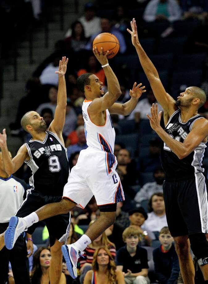 Charlotte Bobcats' Ramon Sessions ( center) tries to shoot between the Spurs' Tony Parker (left) and Tim Duncan during the second half in Charlotte, N.C., Saturday, Dec. 8, 2012. The Spurs won 132-102. Photo: Chuck Burton, Associated Press / AP