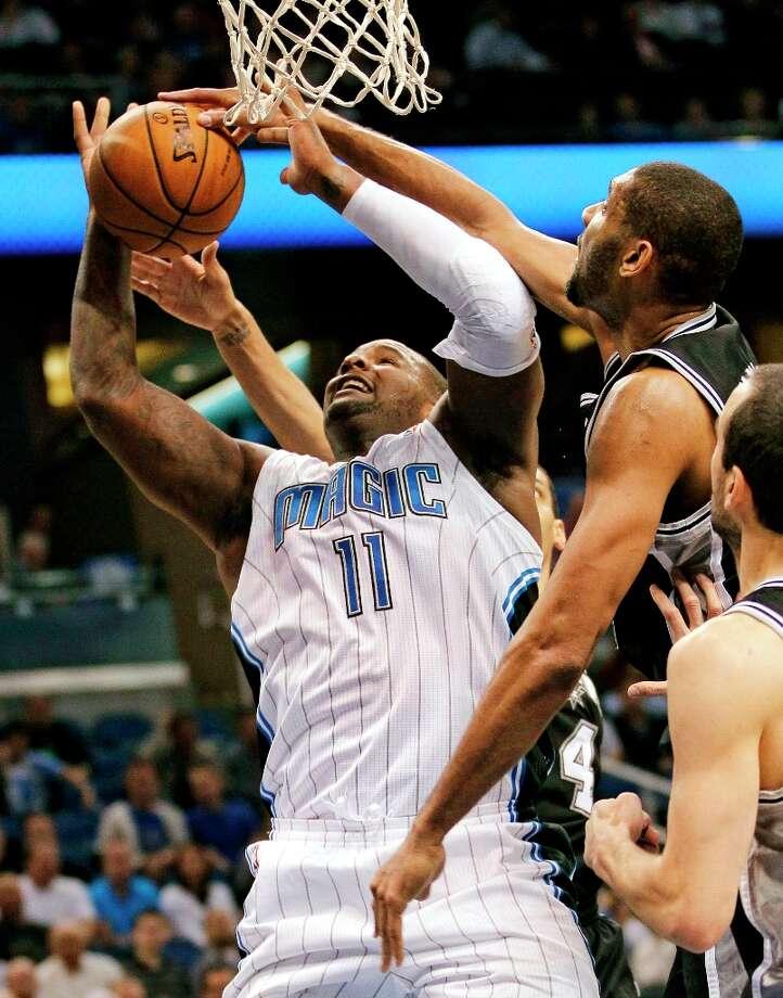 Orlando Magic's Glen Davis (11) shoots as the Spurs' Tim Duncan (center) partially blocks the shot during the first half Wednesday, Nov. 28, 2012, in Orlando, Fla. Photo: John Raoux, Associated Press / AP