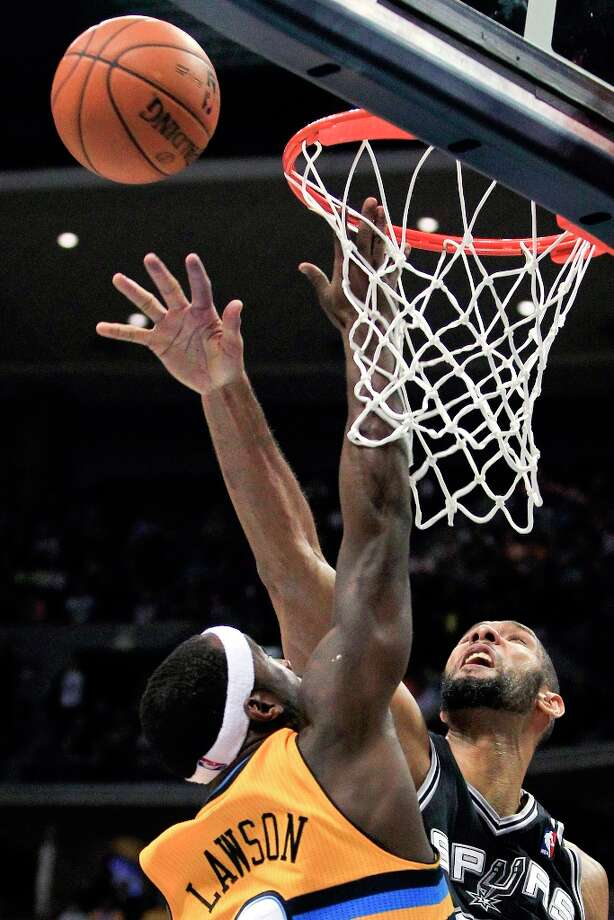 The Spurs' Tim Duncan (right) blocks a shot by Denver Nuggets' Ty Lawson during the third quarter Tuesday, Dec. 18, 2012, in Denver. The Nuggets won 112-106. Photo: Barry Gutierrez, Associated Press / FR170088 AP