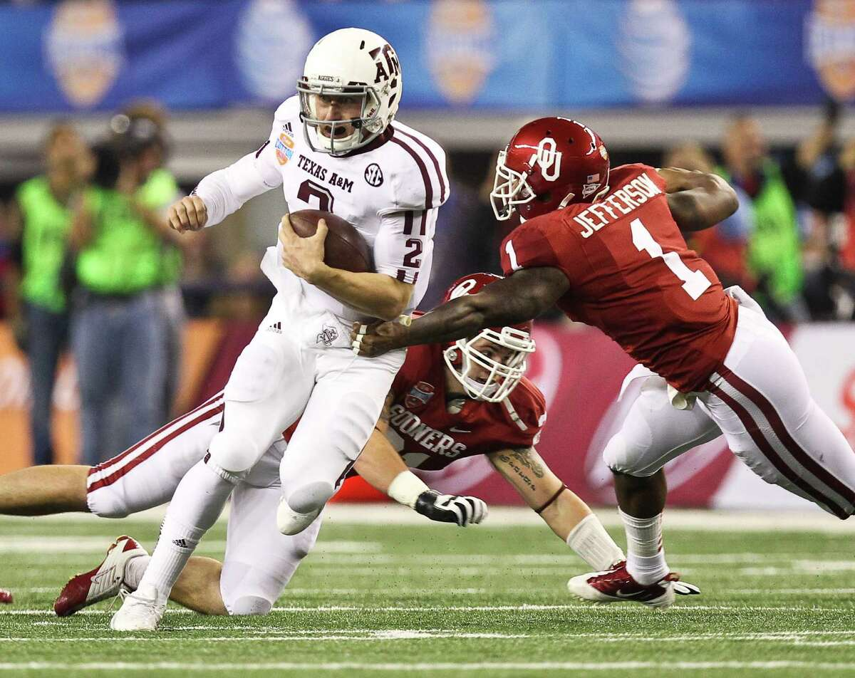 Texas A&M quarterback Johnny Manziel (2) gets past Oklahoma defensive back Tony Jefferson (1) and the rest of the Sooner defense for a first down during the second quarter of the Cotton Bowl college football game, Friday, Jan. 4, 2013, in Cowboys Stadium in Arlington. ( Nick de la Torre / Houston Chronicle )