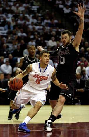 Florida's Scottie Wilbekin (5) drives around Texas A&M's Andrew Young (0) during the first half of an NCAA college basketball game on Thursday, Jan. 17, 2013, in College Station, Texas. (AP Photo/David J. Phillip) Photo: David J. Phillip, Associated Press / AP