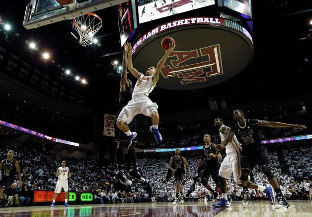 Florida's Scottie Wilbekin (5) shoots as Texas A&M's Elston Turner defends during the second half of an NCAA college basketball game on Thursday, Jan. 17, 2013, in College Station, Texas. Florida defeated Texas A&M 68-47. (AP Photo/David J. Phillip) Photo: David J. Phillip, Associated Press / AP