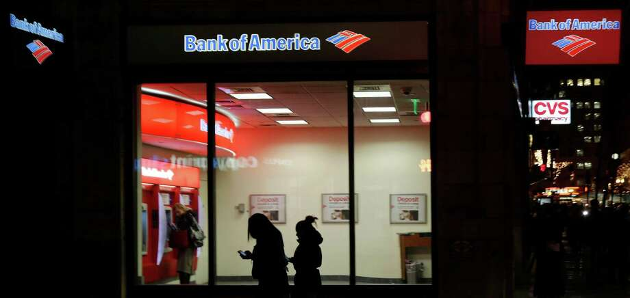 In this Thursday, Dec. 13, 2012 photo people use a Bank of America ATM in Boston. Bank of America says its fourth-quarter earnings shrank as it cleaned up old problems from its mortgage unit.  The bank made $367 million in the last three months of 2012, down from $1.6 billion in the same period a year ago. The earnings were equivalent to 3 cents per share.  (AP Photo/Charles Krupa) Photo: Charles Krupa