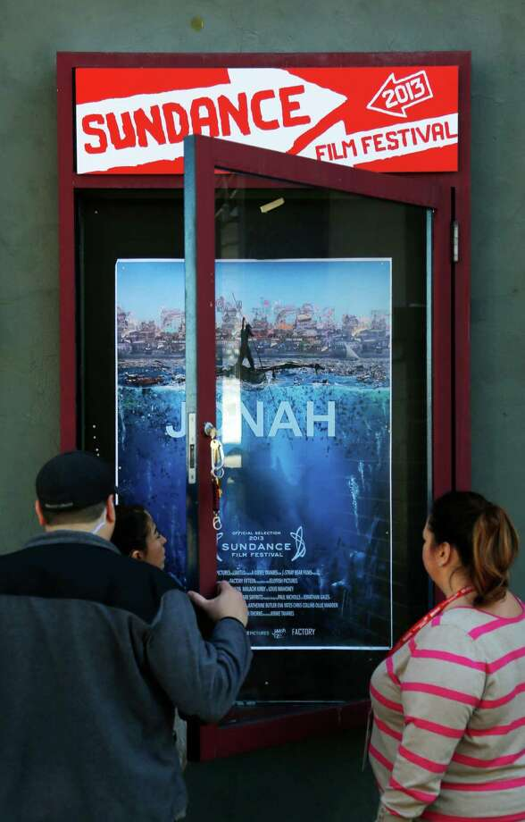 Workers install a movie poster at the Egyptian Theatre on Main Street during the 2013 Sundance Film Festival on Thursday. (Photo by Danny Moloshok/Invision/AP) Photo: Ap/getty