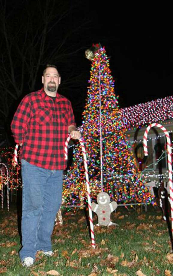 Milford resident Christopher Donnells stands among the festive decorations in front of his Meadows End Road home in Milford Ct. The  Donnells have turned their yard into a holiday wonderland with a bright display to help raise money for the Connecticut Food Bank.  In 2008, the Donnells successfully displayed 40,000 lights on their house.  This year they are increasing the light number to 45,000. The Connecticut Energy Efficiency Fund (CEEF) and the United Illuminating Company (UI) are helping the Donnells help others by providing 25,000 Light Emitting Diode (LED) lights for the 45,000 light display.  CEEF and UI did this as a means of spreading the message of energy efficiency and to help the Donnells' reduce their energy consumption by using energy-efficient LED technology for a holiday display that raises money for a good cause. Photo: Contributed Photo / Connecticut Post Contributed
