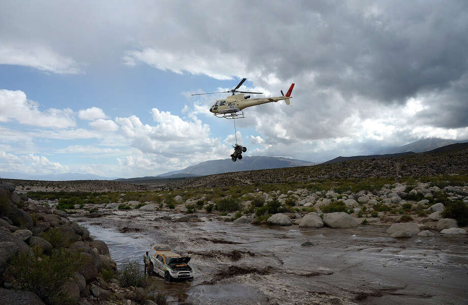 Brazil's Youssef Haddad (L) observes his Mitsubishi stuck in a river below, as a helicopter passes with an unidentified quad, during Stage 8 of the Dakar Rally 2013 between Salta and Tucuman, Argentina, on January 12, 2013. The rally takes place in Peru, Argentina and Chile from January 5-20. Photo: FRANCK FIFE, AFP/Getty Images / 2013 AFP