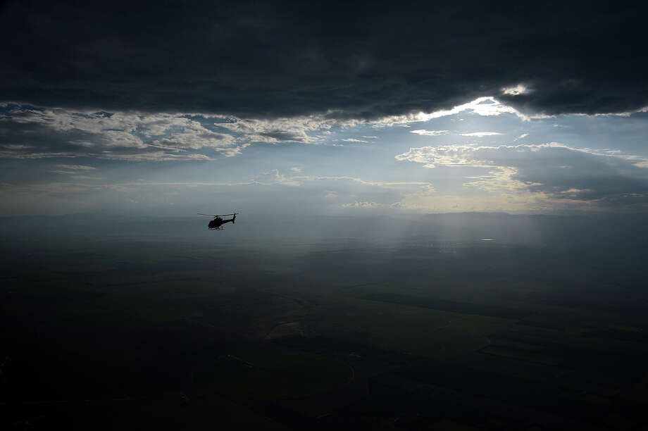 A helicopter overflies Tucuman before the Stage 9 of the Dakar 2013 between Tucuman and Cordoba, Argentina, on January 14, 2013. The rally takes place in Peru, Argentina and Chile between January 5 and 20. Photo: FRANCK FIFE, AFP/Getty Images / 2013 AFP