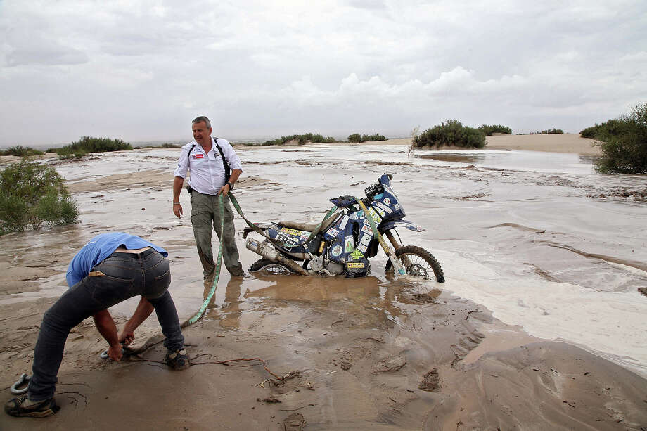 The director of the Dakar Rally 2013 Etienne Lavigne stands next to the Yamaha of French Herve Thierry (out of frame) during the Stage 11 of the Dakar 2013 between La Rioja and Fiambala, Argentina, on January 16, 2013. The rally takes place in Peru, Argentina and Chile between January 5 and 20. Photo: POOL, AFP/Getty Images / 2013 AFP
