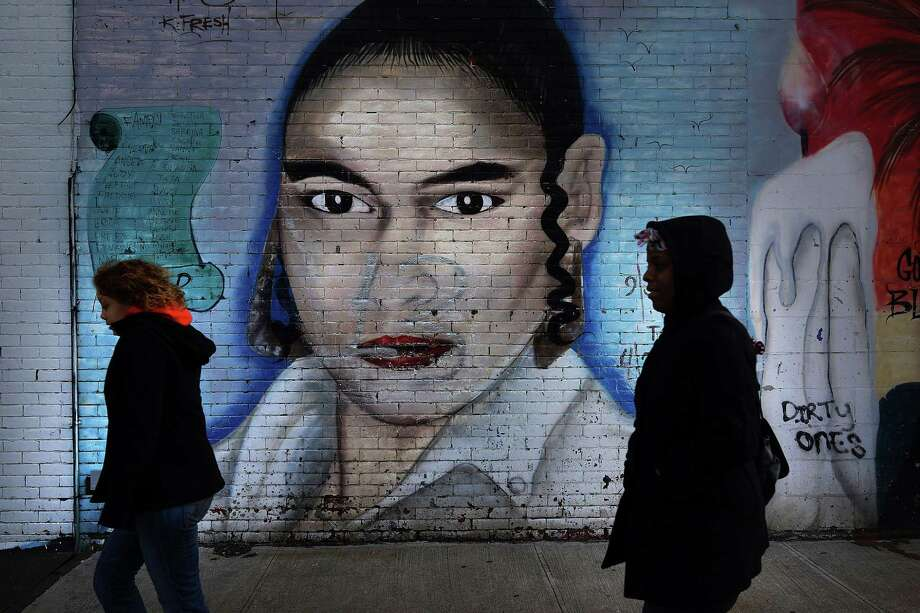 NEW YORK, NY - JANUARY 17: Women walk by a graffiti memorial in memory of a woman in the Bedford-Stuyvesant neighborhood on January 17, 2013 in the Brooklyn borough of New York City. Visual memorials honoring residents who in many cases met violent ends decorate many Brooklyn neighborhoods. New York Governor Andrew Cuomo recently signed into law the New York Secure Ammunition and Firearms Enforcement Act, one of the toughest gun laws in the country. Photo: Spencer Platt, Getty Images / 2013 Getty Images
