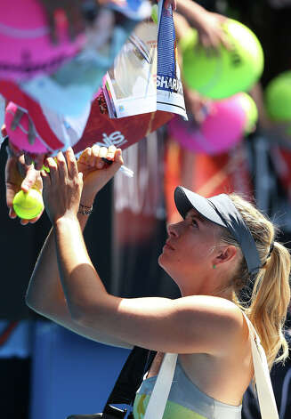 Maria Sharapova of Russia signs autographs after winning her first round match against Olga Puchkova of Russia during day one of the 2013 Australian Open at Melbourne Park on January 14, 2013 in Melbourne, Australia. Photo: Michael Dodge, Getty Images / 2013 Getty Images