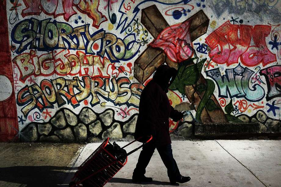 NEW YORK, NY - JANUARY 17:  A woman walks by a graffiti memorial on a wall in memory of an individual killed in the Bedford-Stuyvesant neighborhood on January 17, 2013 in the Brooklyn borough of New York City. Visual memorials honoring residents who in many cases met violent ends decorate many Brooklyn neighborhoods. New York Governor Andrew Cuomo recently signed into law the New York Secure Ammunition and Firearms Enforcement Act, one of the toughest gun laws in the country. Photo: Spencer Platt, Getty Images / 2013 Getty Images