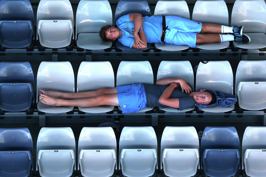 Fans lie across seats in the stands to watch the men's first round match between David Goffin of Belgium and Fernando Verdasco of Spain during day one of the 2013 Australian Open at Melbourne Park on January 14, 2013 in Melbourne, Australia. Photo: Julian Finney, Getty Images / 2013 Getty Images