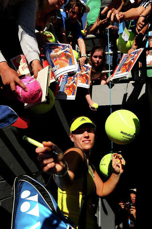 Angelique Kerber of Germany signs autographs for fans after winning her first round match against Elina Svitolina of the Ukraine during day one of the 2013 Australian Open at Melbourne Park on January 14, 2013 in Melbourne, Australia. Photo: Cameron Spencer, Getty Images / 2013 Getty Images