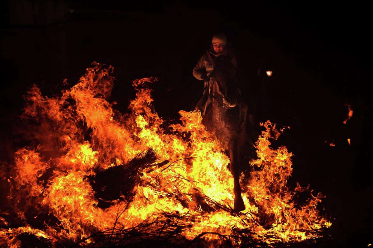 A woman rides a horse through a bonfire in San Bartolome de Pinares, Spain, Wednesday, Jan. 16, 2013, in honor of Saint Anthony, the patron saint of animals. On the eve of Saint Anthony's Day, hundreds ride their horses trough the narrow cobblestone streets of the small village of San Bartolome during the