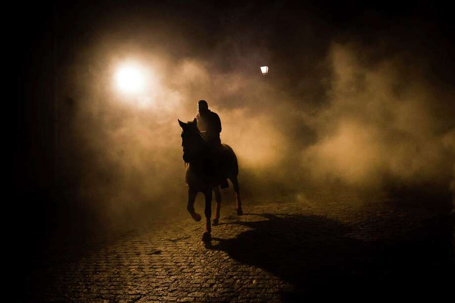 "A man rides a horse trough the smoke in San Bartolome de Pinares, Spain, Wednesday, Jan. 16, 2013, in honor of Saint Anthony, the patron saint of animals. On the eve of Saint Anthony's Day, hundreds ride their horses trough the narrow cobblestone streets of the small village of San Bartolome during the ""Luminarias"", a traditional festival that dates back 500 years and is meant to purify the animals with the smoke of the bonfires, and protect them for the year to come. Photo: Daniel Ochoa De Olza, AP / AP"