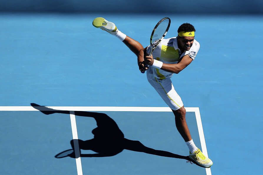 Jo-Wilfried Tsonga of France plays a backhand in his first round match against Michael Llodra of Fra