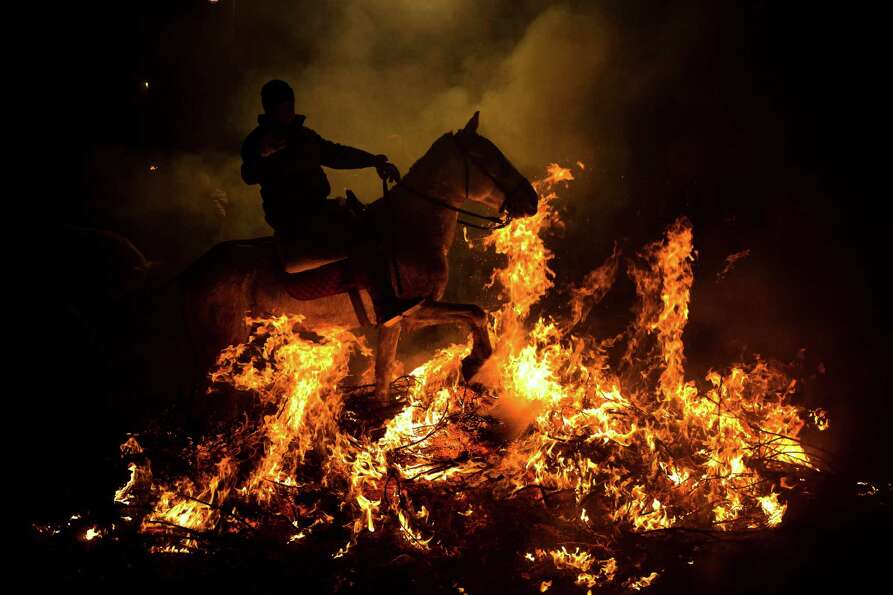 A man rides a horse through a bonfire in San Bartolome de Pinares, Spain, Wednesday, Jan. 16, 2013,