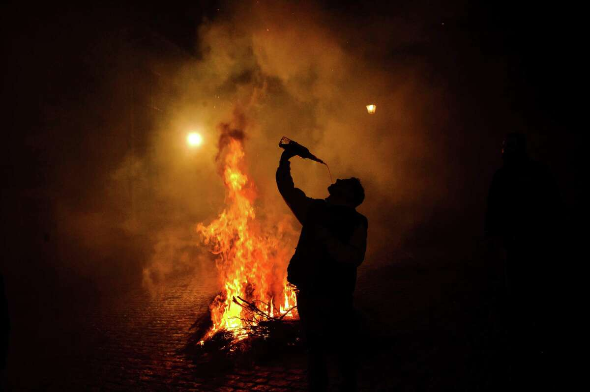 A man drinks wine near a bonfire in San Bartolome de Pinares, Spain, Wednesday, Jan. 16, 2013, in honor of Saint Anthony, the patron saint of animals. On the eve of Saint Anthony's Day, hundreds ride their horses trough the narrow cobblestone streets of the small village of San Bartolome during the
