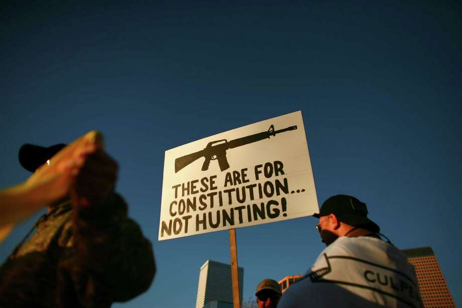 People hold signs during a recent pro-gun rally outside the Colorado State Capitol in Denver. Our  readers continue to weigh in on the debate. Photo: Matthew Staver, New York Times / NYTNS