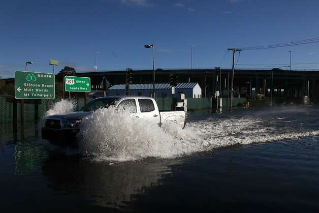 "A pickup truck braves the water logged road after a record high tide known as a ""king tide"" floods roads near the Manzanita Park And Ride on Wednesday Dec. 12, 2012 in Mill Valley, Calif. Photo: Mike Kepka, The Chronicle"